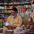 General store keeper tends to paperwork at Empress Market Karachi Pakistan